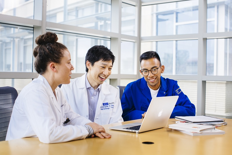 Three stem cell center trainees look at data on a laptop
