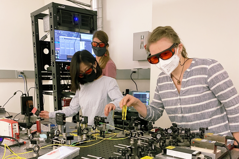 Image of two Ph.D. students in the Quantum Biology Tech lab at UCLA with Clarice Aiello, who leads the lab